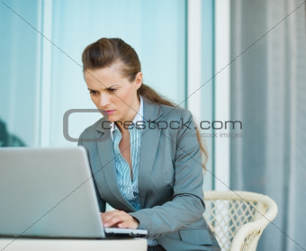 Business woman working on laptop on hotel terrace