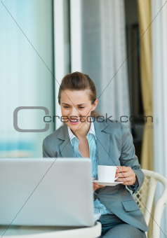 Business woman drinking coffee and looking in laptop