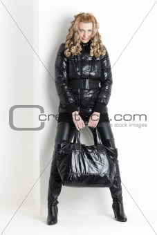 standing woman wearing black clothes holding a handbag