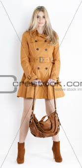 standing woman wearing coat and fashionable brown shoes with a handbag