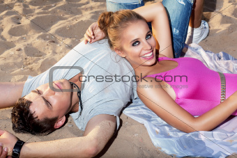 Happy couple lying together on sand - romance and friendship