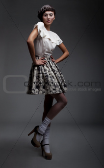 Luxurious young woman posing on podium in retro clothes