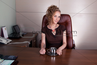 Attractive business lady sitting at office table with cup of tea