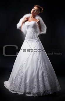 Beautiful bride in wedding dress and boa on podium posing