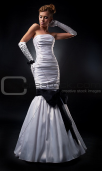 Lovely fiancee in white nuptial dress and gloves studio shot