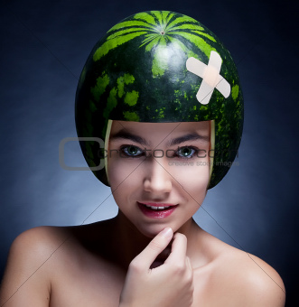 Pretty cute - young girl with watermelon as hard hat close up