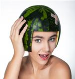 Fancy young happy girl with fresh green melon as a hard hat