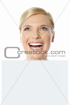 Thoughtful smiling woman holding whiteboard