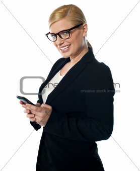 Smiling female business executive messaging