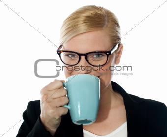 Attractive corporate female drinking coffee