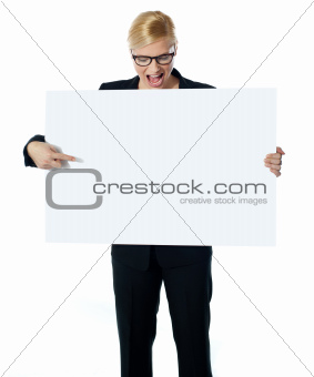 Successful business female pointing at white blank billboard
