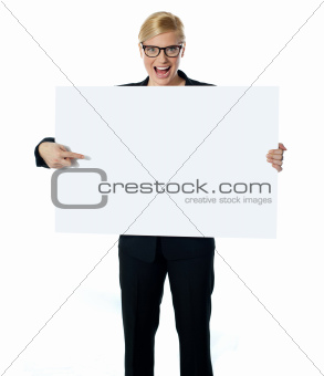 Saleswoman pointing at blank billboard