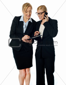 Two females looking at progress report and discussing