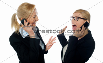 Happy businesswomen communicating on cellphone