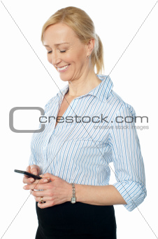 Smiling young corporate lady messaging
