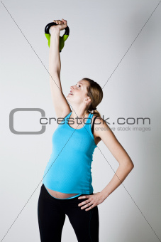 Pregnant woman exercising with kettlebell