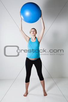 Pregnant woman stretching with fitness ball