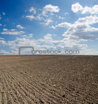black ploughed field under blue sky