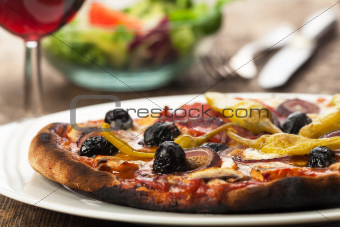 closeup of a pizza with red wine 
