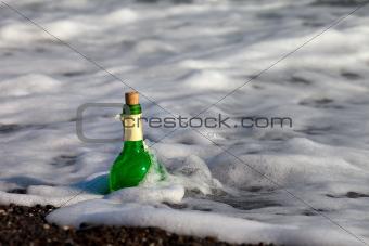 Bottle of wine in sea surf