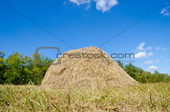 stack of straw under deep blue sky