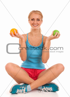 Beautiful young woman holding an apple and orange