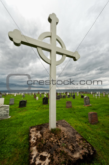 Graveyard cross under storm clouds