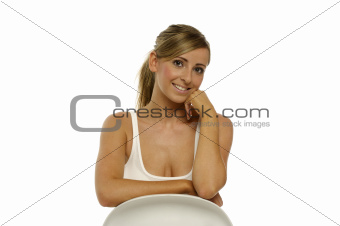 Beautiful young woman sitting isolated on a white background