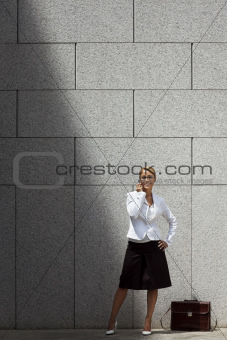 attractive woman speaking on telephone near office building