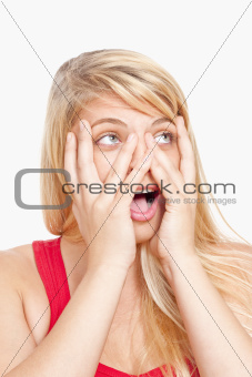 surprised young girl covering face with her hands peeking through fingers