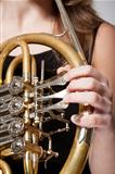 detail of a female musicians fingers playing concert french horn 