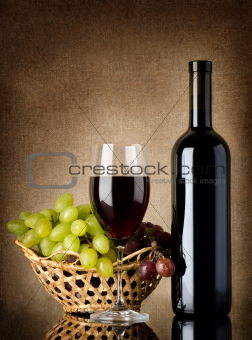 Wine and grapes on a old background