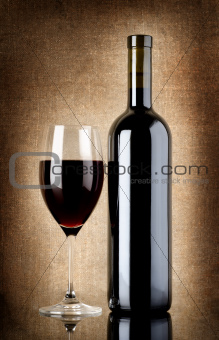 Wine bottle and wineglass on a old canvas