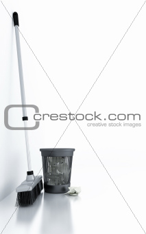 brush and a bucket of garbage in an empty light room