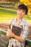 Outdoor Portrait of a Pretty Mixed Race Female Student Holding Books Looking Away.