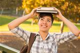 Portrait of a Pretty Mixed Race Young Female Holding Books on Her Head Outdoors at the Park on a Sunny Afternoon.