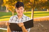 Portrait of a Pretty Mixed Race Female Holding Open Book Outdoors at the Park on a Sunny Afternoon.
