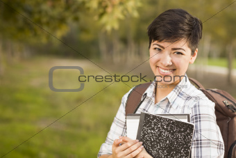 Outdoor Portrait of a Pretty Mixed Race Female Student Holding Books on a Sunny Afternoon.