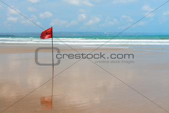 Red flag on beach with no swimming notes.