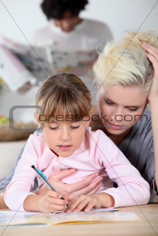 Baby-sitter and little girl doing homework