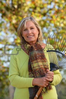 Woman raking leaves in a yard