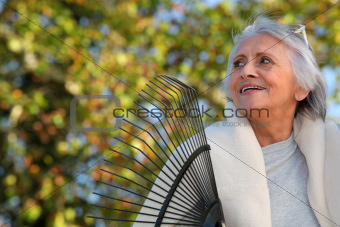 Elderly lady raking leaves in her garden