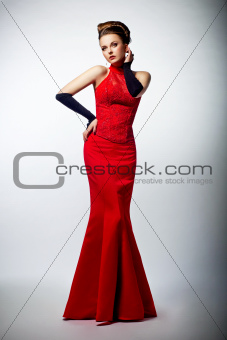 Tempting sexy slim female in sensual red long dress posing