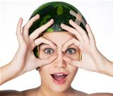 Funny young girl with ripe watermelon as a helmet on her head