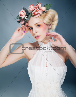 Lovely blonde princess with wreath of flowers on her head