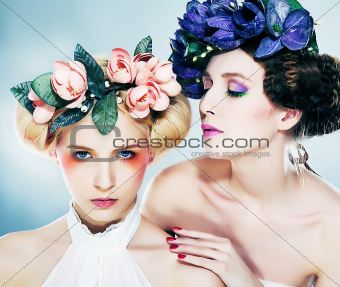 Two sensual nymphs in colorful wreaths closeup portrait