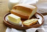 butter,  loaf of white bread and milk on wooden plate