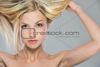 Portrait of blond girl rising up hair