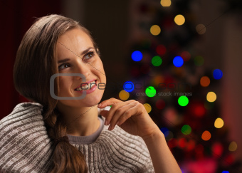 Portrait of thoughtful woman with Christmas tree in background
