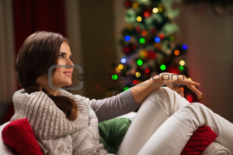 Thoughtful woman sitting on chair in front of Christmas tree|elegant